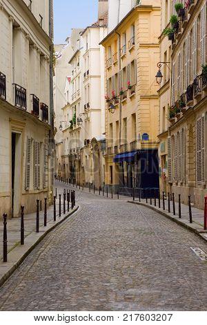 A quaint deserted cobbblestone street in Paris.