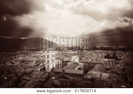 Lucca town skyline rooftop view with Bell Tower of Basilica di San Michele and sun ray in Italy.