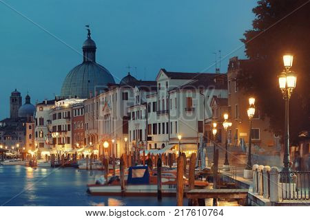 Venice canal view at night with San Simeone Piccolo and historical buildings. Italy.