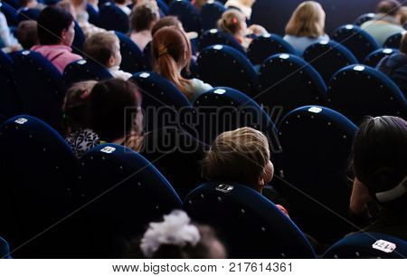 Children and parents watching the theatrical performance. The audience in the theatre.