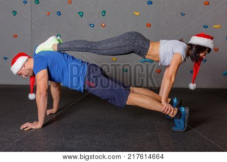Two young athletes, a guy and a girl dressed in red Christmas caps, doing exercises, stand in a double sports static bar. Against the background of the wall for rock climbing. Indoors.