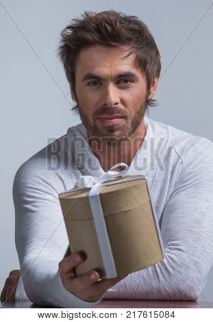 Handsome mid age man stretching out a gift box