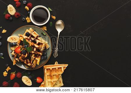 Belgian waffles with berries and fruits on black background. Top view on checkered biscuits with chocolate topping, copy space. Sweet food and tasty breakfast concept