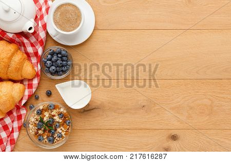 Rich continental breakfast background. French crusty croissants, muesli, tea pot, sweet berries and hot coffee for tasty morning meals. Delicious start of the day. Top view, copy space on natural wood