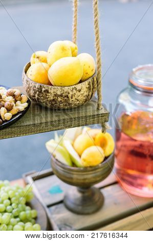 products, healthy lifestyle, countryside concept. delicate yellow apricots lying on the top shelf of wooden counter, under it there is vase with some fruits and fresh compot of beautiful pinky colour