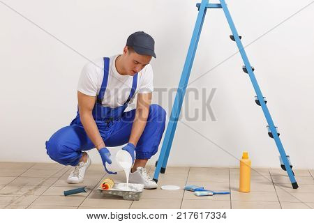 A male painter in blue uniform, pouring white paint from a jar into a plastic pallet. Indoor in the house.