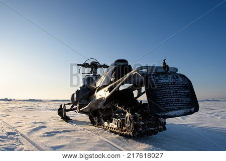 The snowmobile stands on the ice of the lake in clear weather