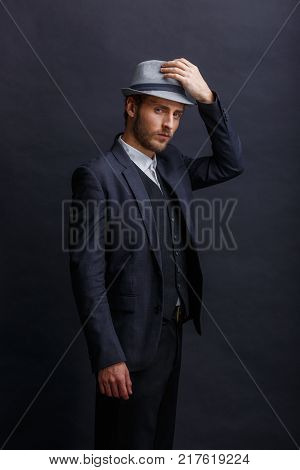 A serious young European man, a dark-haired man in a black suit, stands sideways and, with a serious look, adjusts his hat to himself. On a black background.