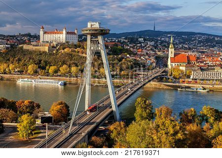 Cityscape of Bratislava with main symbols of the city: castle SNP bridge over Danube river St.Martin´s church and broadcast tower in background. Warm sunset light.