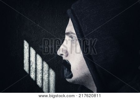 male prisoner with hoodie and covered mouth by black tape to forbidden him the free speeching in front of grunge prison cell