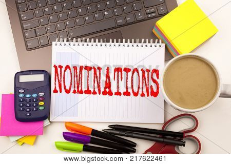 Word writing Nominations in the office with  laptop, marker, pen, stationery, coffee. Business concept for Election Nominate Nomination Workshop white background with space