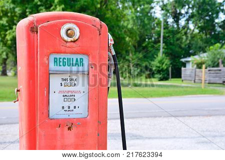 Old rusty american gas pump displaying the price in dollars and filling amount in gallons.