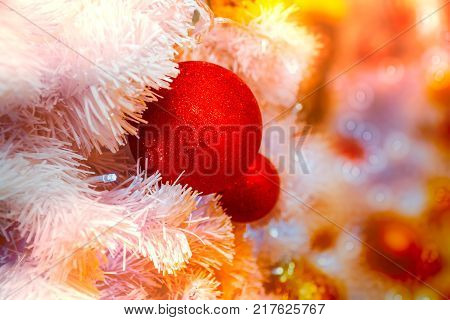 Close-up shot of Christmastide decoration with red balls and white fir tree on golden lighting bokeh background.