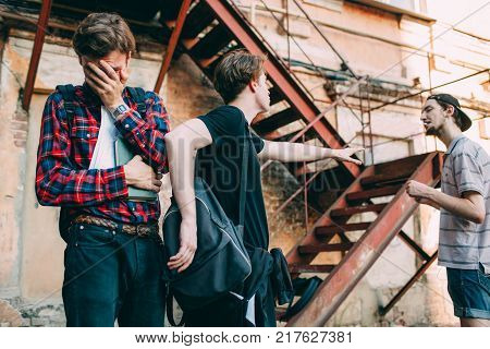 teenager protects his friend from aggressive bully. Social youth problems. Scared crying smart boy. True friendship loyalty and support concept.