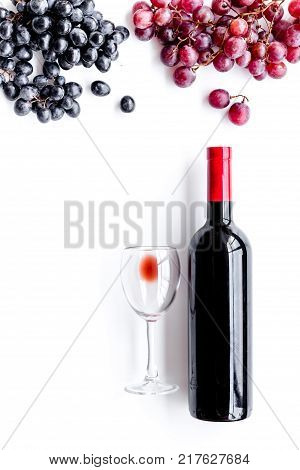 Taste red wine. Bottle of red wine, glass and black grape on white background top view.