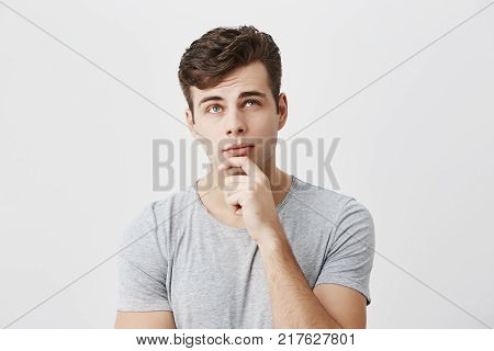 Hmm not bad. Close up studio portrait of concentrated thoughtful male student evaluating his chances to pass exam, keeps hand on chin, tries to decide what he deserves. People, lifestyle, face expressions.