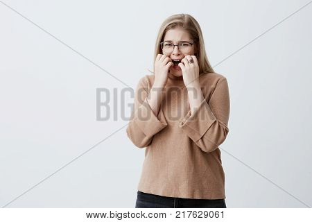 Nervous desperate upset female with blonde hair gestures with hands in anger, being irritated on boyfriend who is late for date. Sad crying woman hates something, shows negative emotions and feelings
