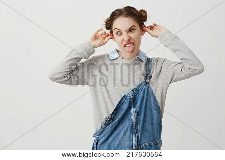 Funny-looking woman wearing denim jumpsuit grimacing making ears protruding. Sassy female rebel with trendy hairstyle being crazy fooling around. Merriment, fun concept