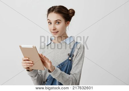 Caucasian woman being girlish with odango buns looking on camera with delighted gaze holding notebook. Positive emotions of female buyer testing new digital tablet. Technology, future