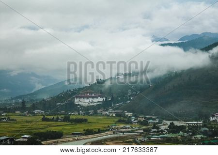 View Of Rinpung Dzong On A Dramatically Cloudy Day In Paro Valley, Bhutan