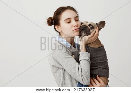 Sentimental woman pressing her cheek to french bulldog being isolated over white background. Female pet owner expressing care and love hugging her pedigree dog while walking in park. Copy space poster
