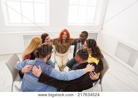 Group therapy. People having group hug during therapy in rehab at multiethnic psychology support meeting, copy space