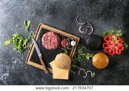 Ingredients for cooking hamburger. Meat beef burger board, cheese, ketchup sauce, tomato, black and white buns, arugula salad over dark texture background. Top view with space. Homemade fast food
