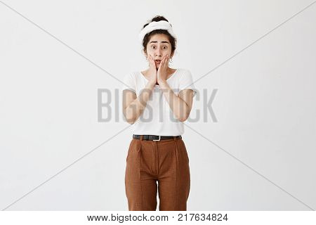 Horizontal portrait of dark-haired stupefied girl keeps mouth opened, with popped eyes, has upset expression, dressed casually, being confused or worried, sees no way out in difficult situation