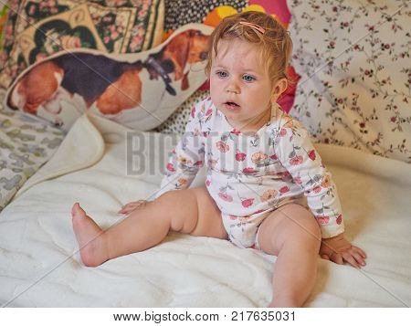 Baby girl blonde in children's room plays on a large bed