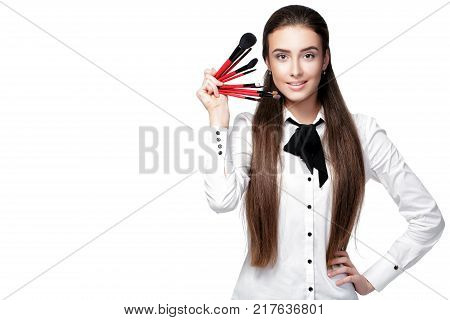 beautiful woman make-up artist with natural make-up holding makeup brush on white background