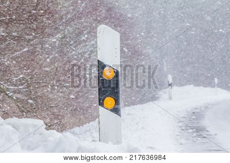 Reflector post at snowy slippery icy white snow winter road. The street track is slick and frozen. High dangerous risk of an accident through the blizzard snowstorm and severe weather at christmas time season.