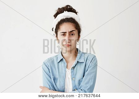 Serious unhappy girl wearing do-rag on her wavy dark hair has appealing face expression, frowns face in dissatisfaction, isolated against studio background. Human negative emotions and feelings concept