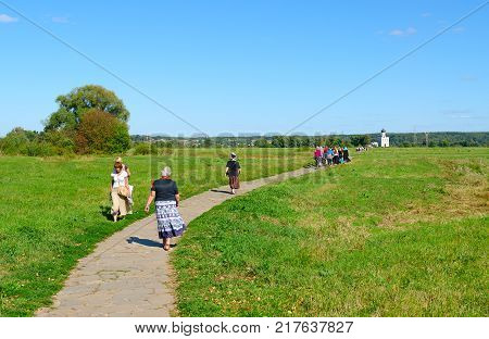 BOGOLUBOVO RUSSIA - AUGUST 21 2015: Unknown people walk along footpath of Bogoliubov meadow to famous Church of Intercession on Nerl Vladimir Region Golden Ring of Russia