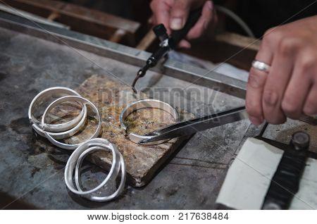 Jeweler at work in jewelery workshop. Jeweller working with bracelet