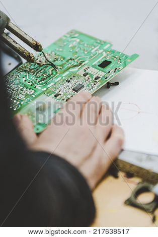 Man Repairing Electronic Circuitr Using Welder Tool