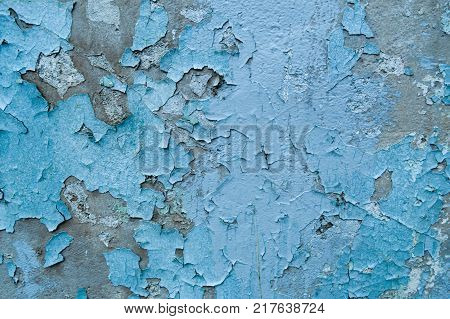 Old blue exfoliated peeling paint on the concrete wall. The background. Texture.