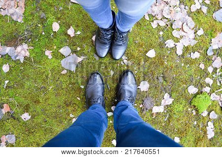 Boots of a man and a woman against a background of green moss and autumn leaves. Male and female legs. The socks are pointed at each other. View from above.