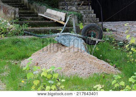 Heavily used construction cart with two handles and single wheel turned upside down on small sand pile after completing work and surrounded with high uncut grass and stone yard