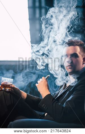Man vaping fumes and drinking alcohol to relax. Unwinding pleasure and chilling concept