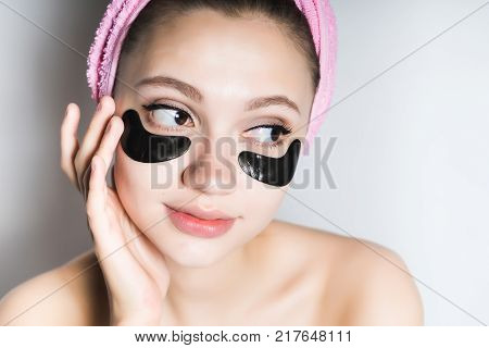 beautiful young girl with a pink towel on her head takes care of herself, under the eyes of black silicone patches