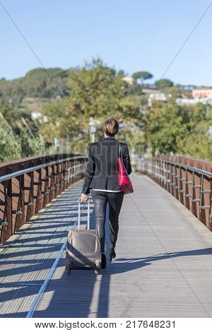 Businesswoman with trolley bag walking in urban environment. Wearing a red bag