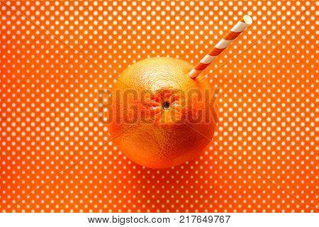 Grapefruit juice, minimalistic concept of grapefruit juice on an orange background with white dots. Flat lay