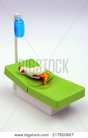 Amsterdam, The Netherlands-  December 10, 2017: Playmobil chicken infected with the bird flu virus lys sick l on a hospital bed.