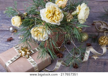 Christmas decoration. Gift, candles, lights, golden balls on a wooden rustic table. Xmas composition of pine branches and English roses in a vase. Golden and brownish aesthetics. poster