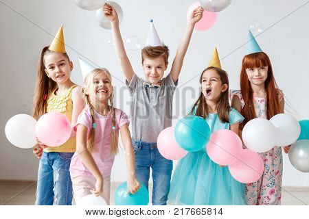 Group of small children have birthday party, wear festive hats, hold balloons, have joy together, enjoy playing games. Small adorable girl celebrates her birthday, invites friends, have happy looks