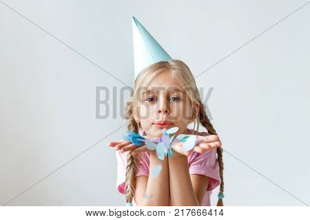 Indoor shot of pretty small kid with long pigtails, wears cone hat on head, blows colourful sheet of paper, looks into camera, celebrates her anniversary, isolated over white studio background
