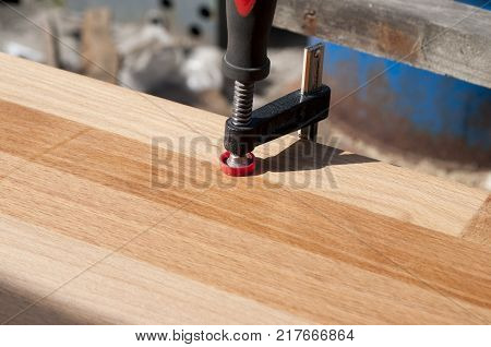 Clamped pieces of wood with c-clamps and bar clamp , wooden parts in the carpentry workshop