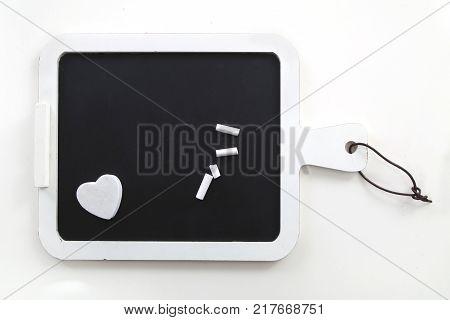 heart shaped white eraser on blackboard white background