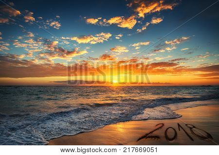 Happy New Year 2018 concept lettering on the beach. Sunrise over the beach. Punta Cana