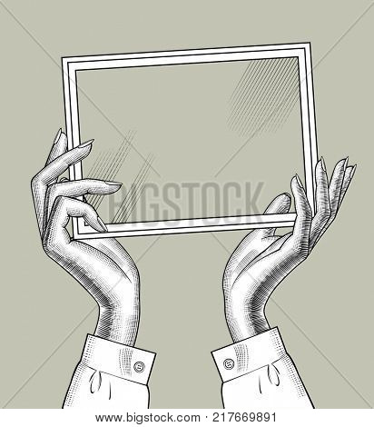 Hands of woman holding a rectangular frame with glass. Vintage engraving stylized drawing. Retro concept poster and banner